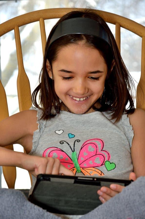 La petite fille hispanique apprécie sa tablette neuve photos stock
