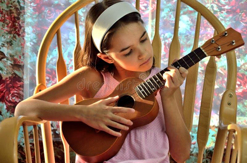 La petite fille hispanique joue l'ukulélé images stock