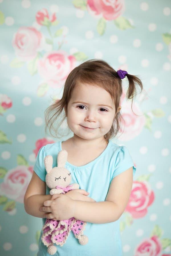 La petite fille jouant avec elle a tricoté des jouets photo stock