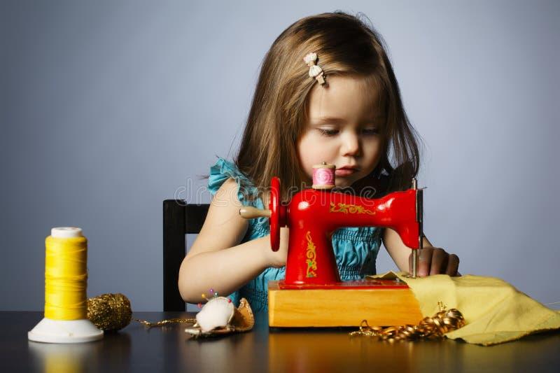 La petite fille joue avec la machine à coudre photographie stock libre de droits