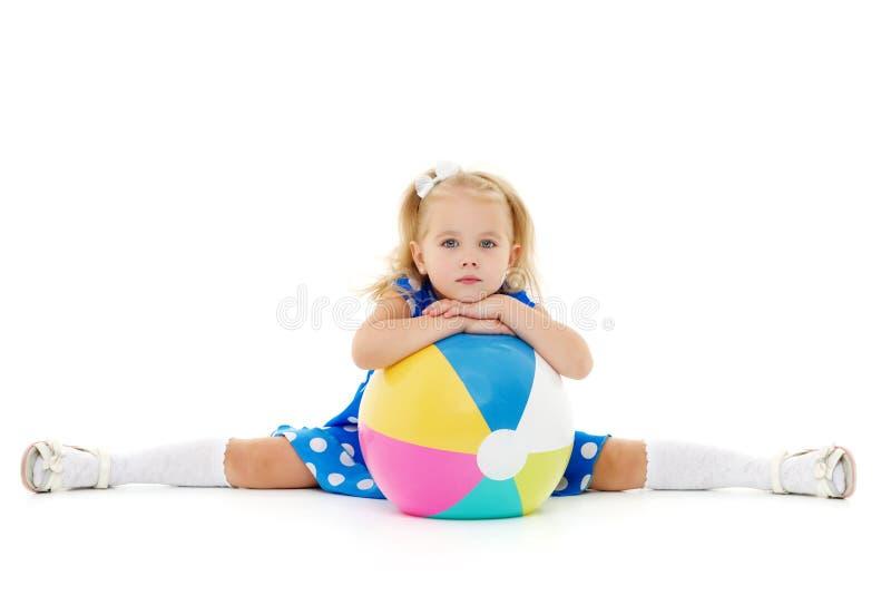 La petite fille joue avec une boule photographie stock