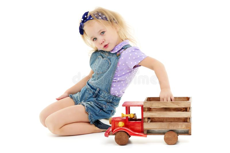 La petite fille joue avec une voiture en bois images stock