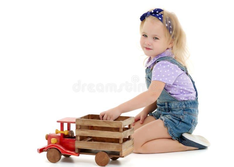 La petite fille joue avec une voiture en bois photographie stock libre de droits