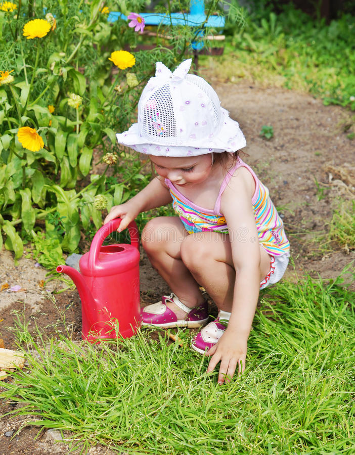 La petite fille joue dans le jardin photo stock