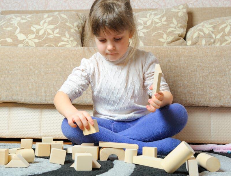 La petite fille joue les cubes en bois en jouet photos stock