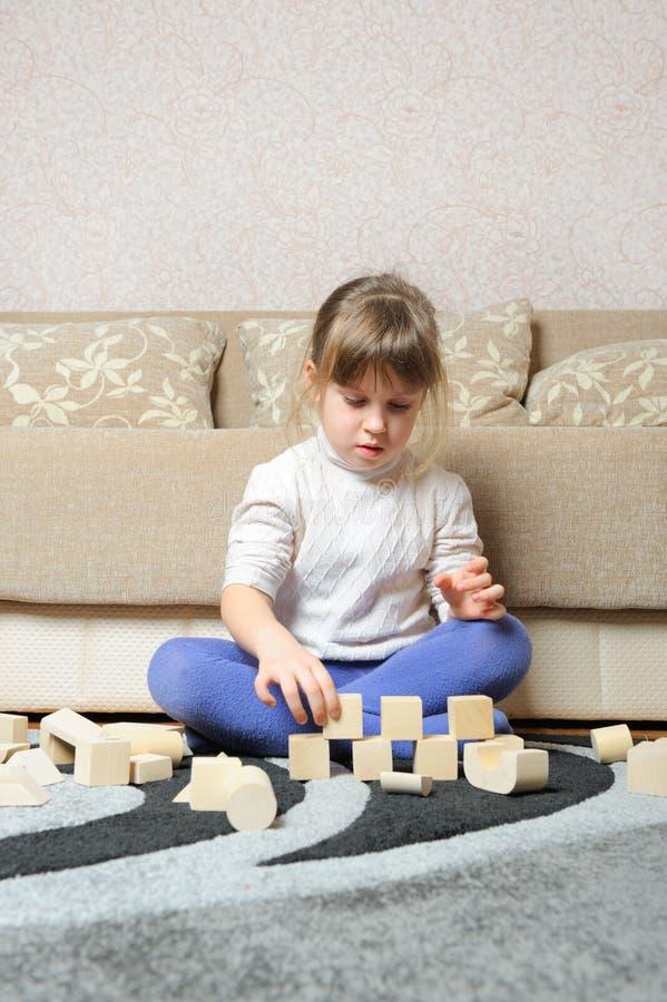 La petite fille joue les cubes en bois en jouet photographie stock libre de droits