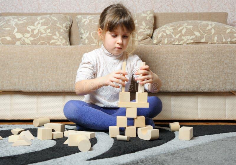 La petite fille joue les cubes en bois en jouet image stock