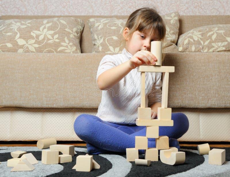 La petite fille joue les cubes en bois en jouet images libres de droits