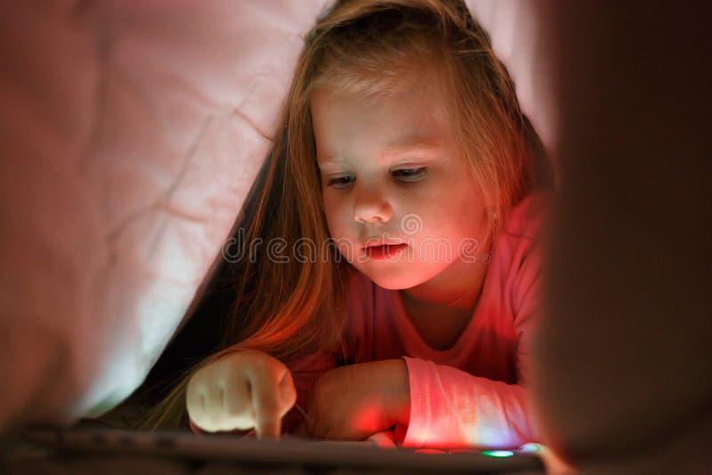 La petite fille joue sur le comprimé dans le secret de ses parents la nuit sous la couverture photos libres de droits