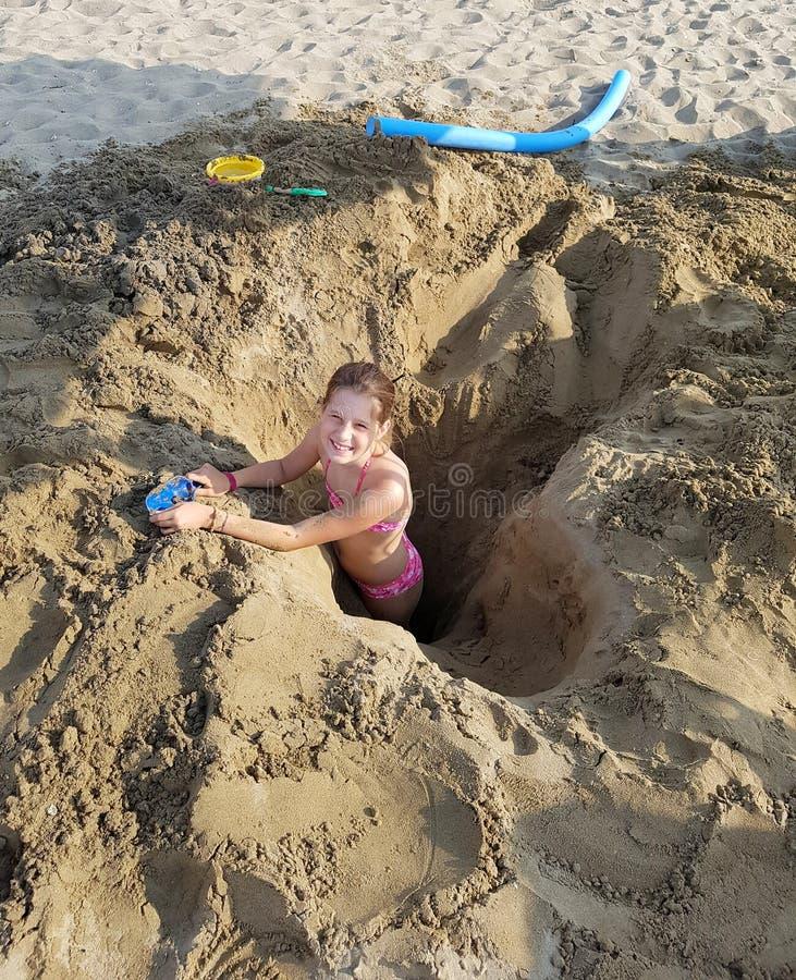 La petite fille joue sur un trou dans la plage photos stock