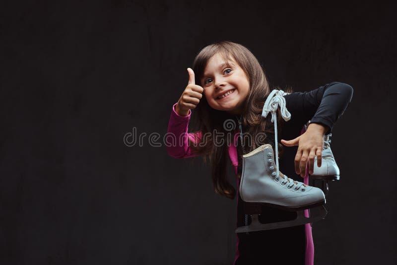 La petite fille joyeuse s'est habillée dans les vêtements de sport tient des pouces d'expositions de patins de glace  D'isolement image libre de droits