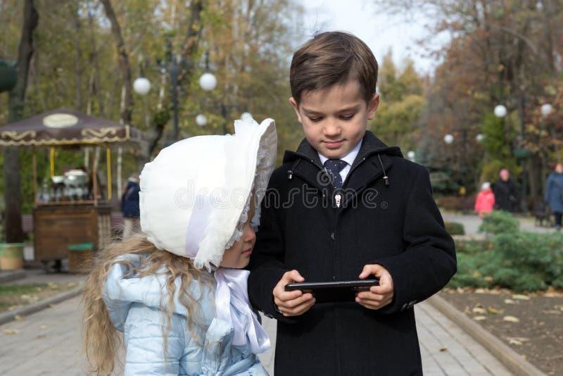 La petite fille a l'air intéressante sur l'écran du gadget, que son frère tient dans ses mains Des enfants heureux qui ont l'air photographie stock