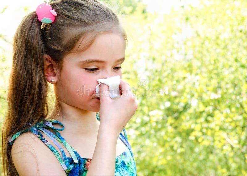 La petite fille a l'allergie à jaillir fleurissant et soufflant ses no. photo stock