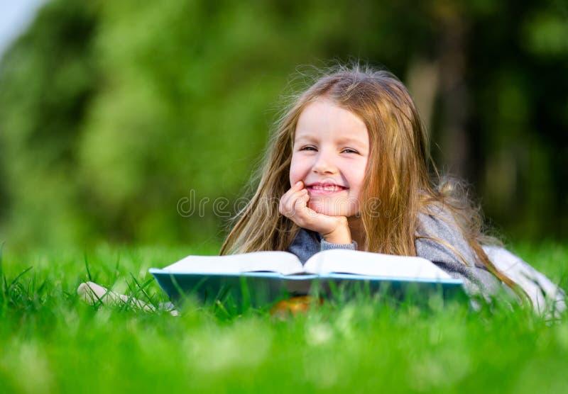 La petite fille lit le livre sur l'herbe photographie stock libre de droits