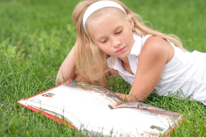 La petite fille lit le livre sur l'herbe images stock