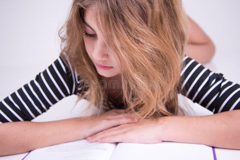 La petite fille a lu un texte dans le livre photos libres de droits