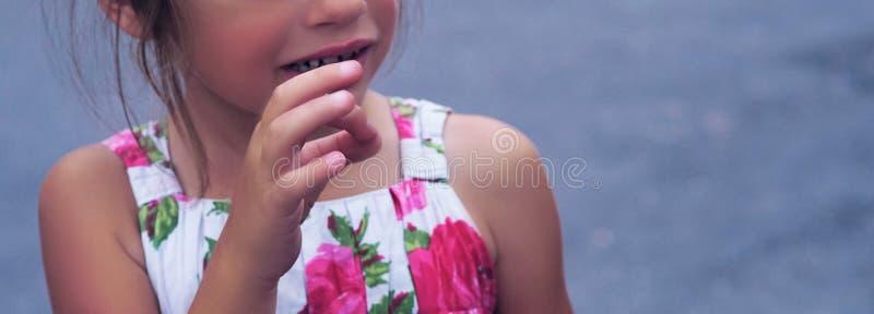 La petite fille lui montre des mains après craie de dessin sur l'asphalte photo stock