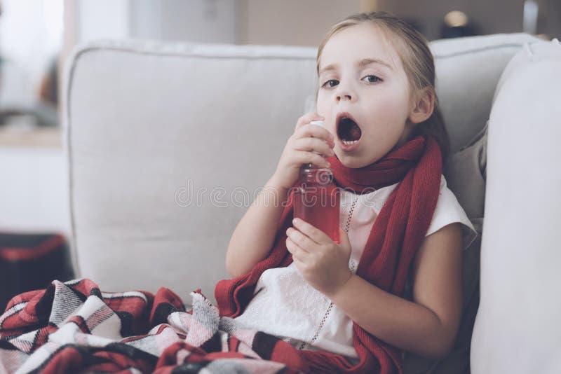 La petite fille malade s'assied sur un divan blanc enveloppé dans une écharpe rouge Elle éclabousse sa gorge d'un pulvérisateur m photos libres de droits