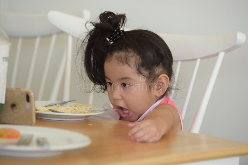 La petite fille mange de la nourriture délicieuse images libres de droits