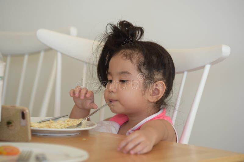 La petite fille mange de la nourriture délicieuse photographie stock