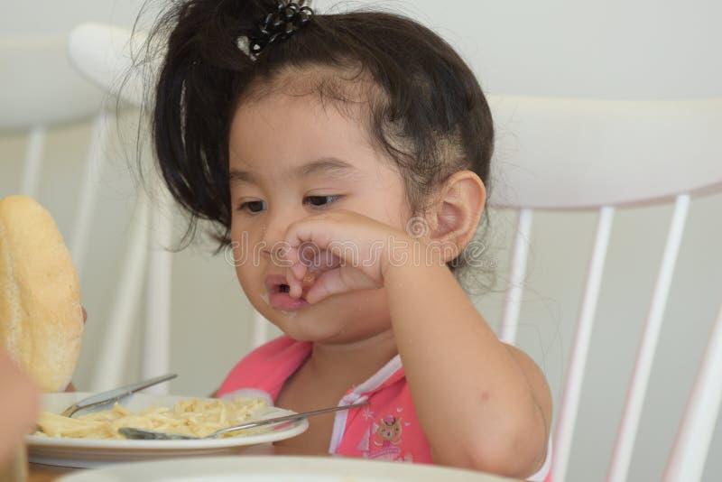 La petite fille mange de la nourriture délicieuse image stock