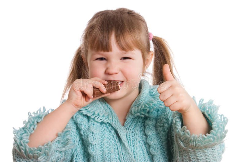La petite fille mange du chocolat photo stock