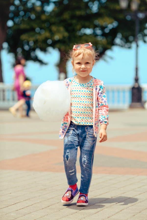 La petite fille mange la sucrerie de coton dans la perspective de la mer image libre de droits