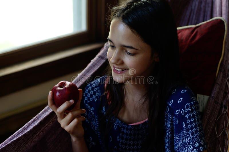 La petite fille mange une pomme dans un hamac photos libres de droits