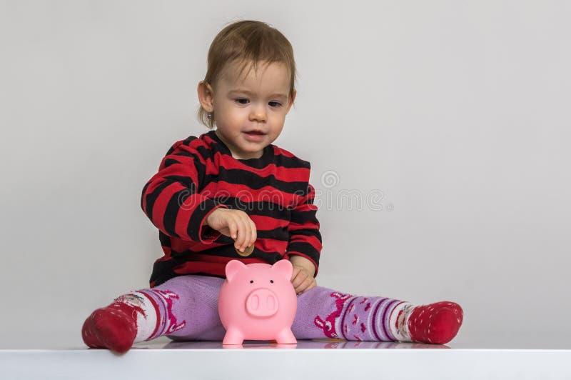 La petite fille met des pièces de monnaie à la banque porcine d'argent L'épargne et concept d'opérations bancaires photo libre de droits