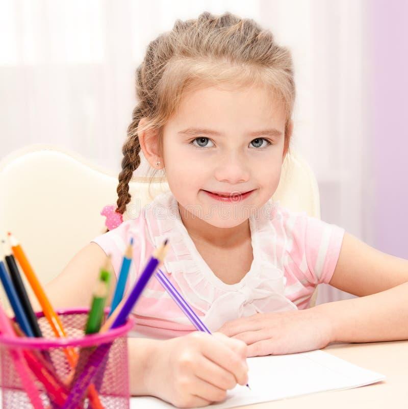 La petite fille mignonne écrit au bureau images stock