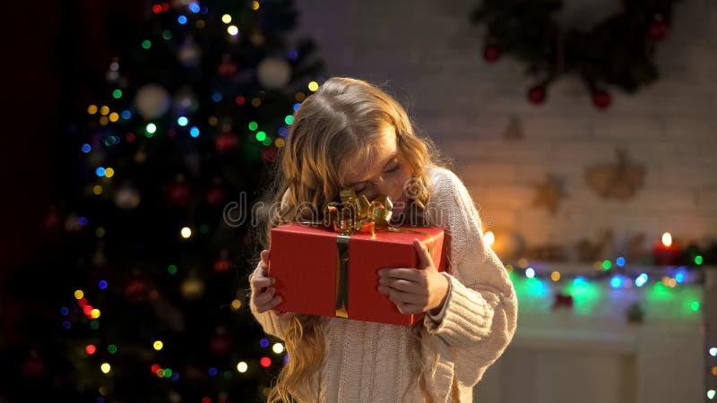 La petite fille mignonne étreignant le cadeau de Noël, rêve viennent l'atmosphère vraie et de fête photographie stock