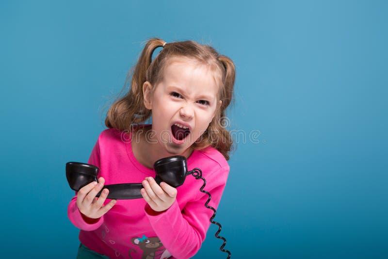 La petite fille mignonne attirante dans la chemise rose avec le singe et les pantalons bleus parle un téléphone photo libre de droits