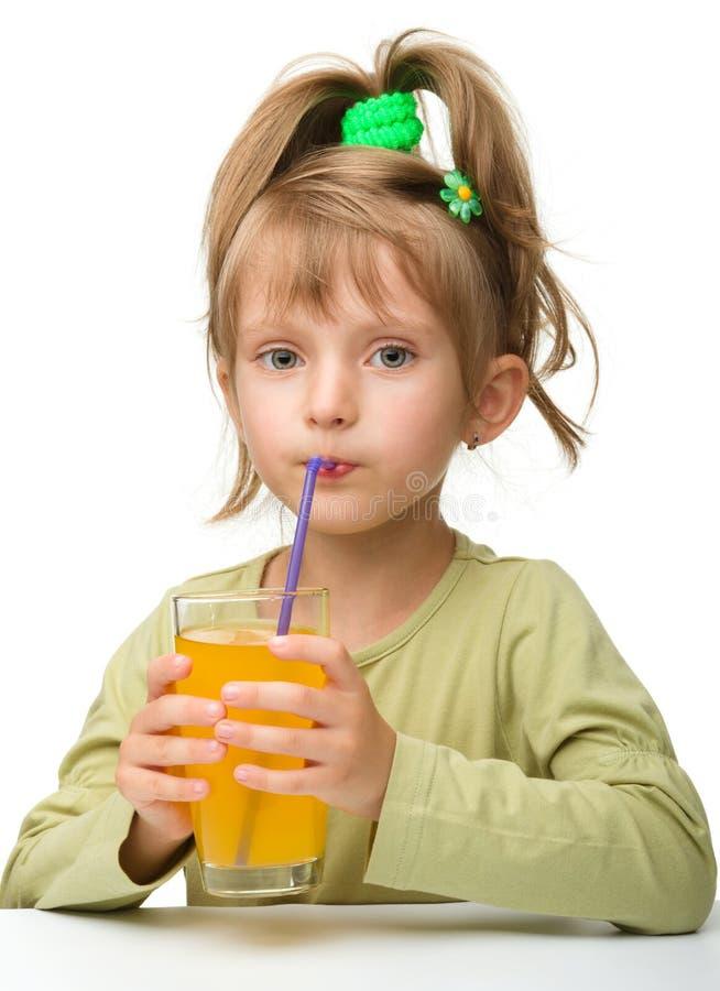La petite fille mignonne boit du jus d'orange images libres de droits