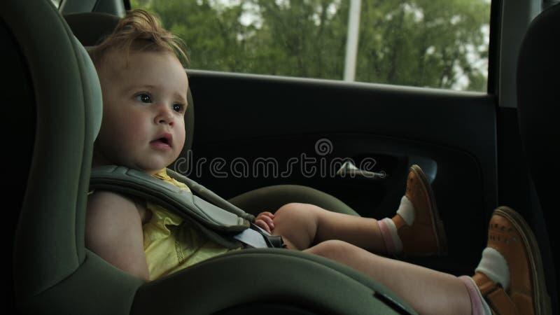 La petite fille mignonne conduit avec la famille au siège de sécurité pour enfants de voiture images stock