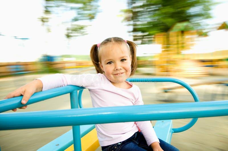 La petite fille mignonne conduit sur le manège image stock