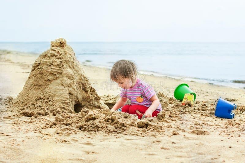 La petite fille mignonne construit une maison hors du sable image stock