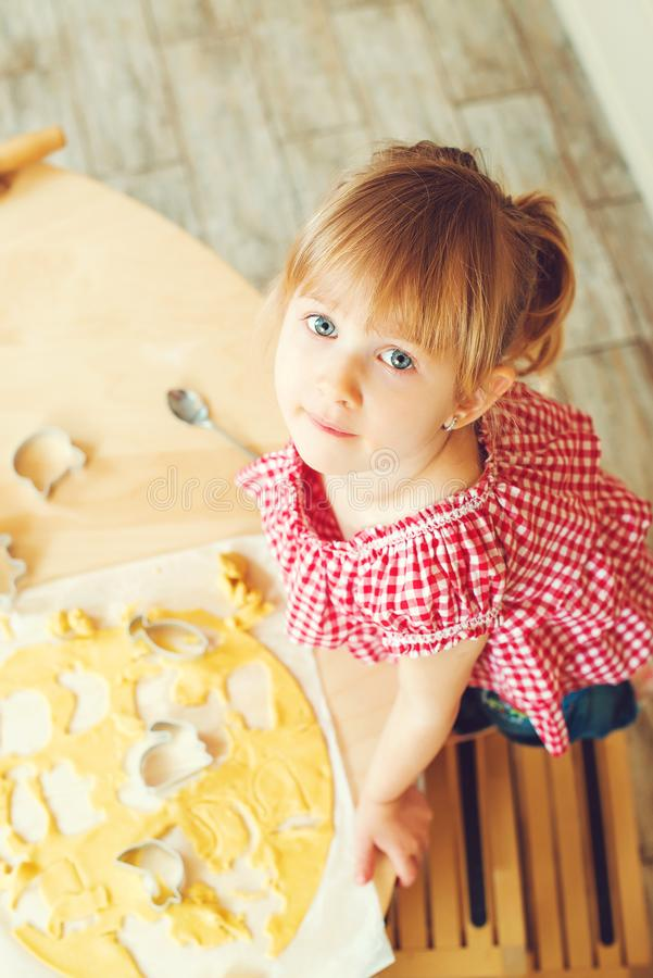 La petite fille mignonne coupe la pâte de biscuit dans différentes formes La fille aide sa mère à faire des biscuits cuire au fou photos stock