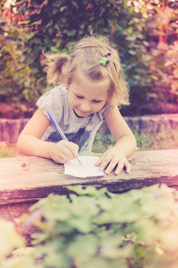 La petite fille mignonne dessine sur le papier dans le jardin image stock
