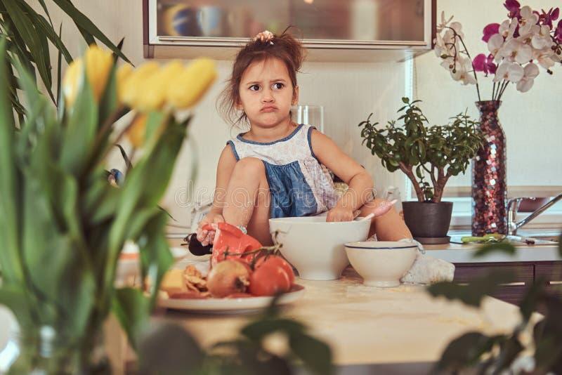 La petite fille mignonne douce apprend à faire cuire un repas dans la cuisine photo libre de droits