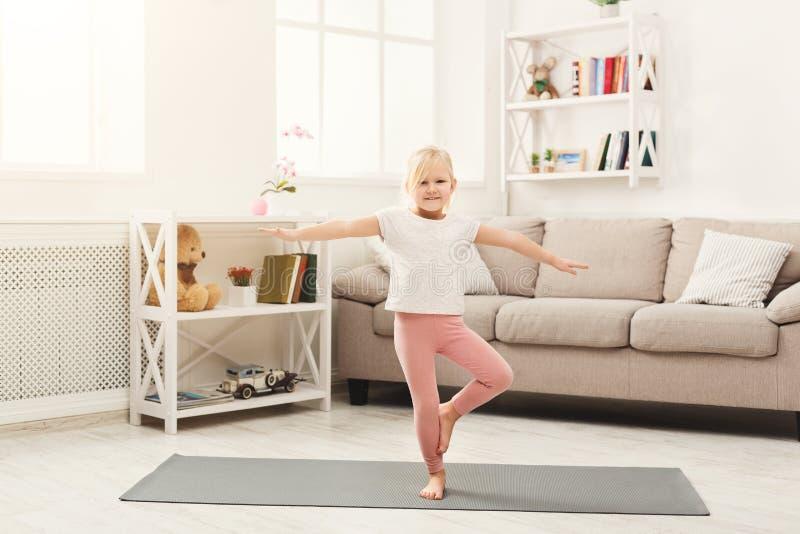 La petite fille mignonne faisant le yoga s'exerce à la maison photos libres de droits