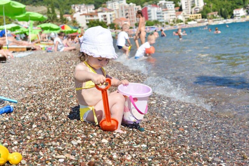 La petite fille mignonne joue avec le seau sur une plage photographie stock libre de droits