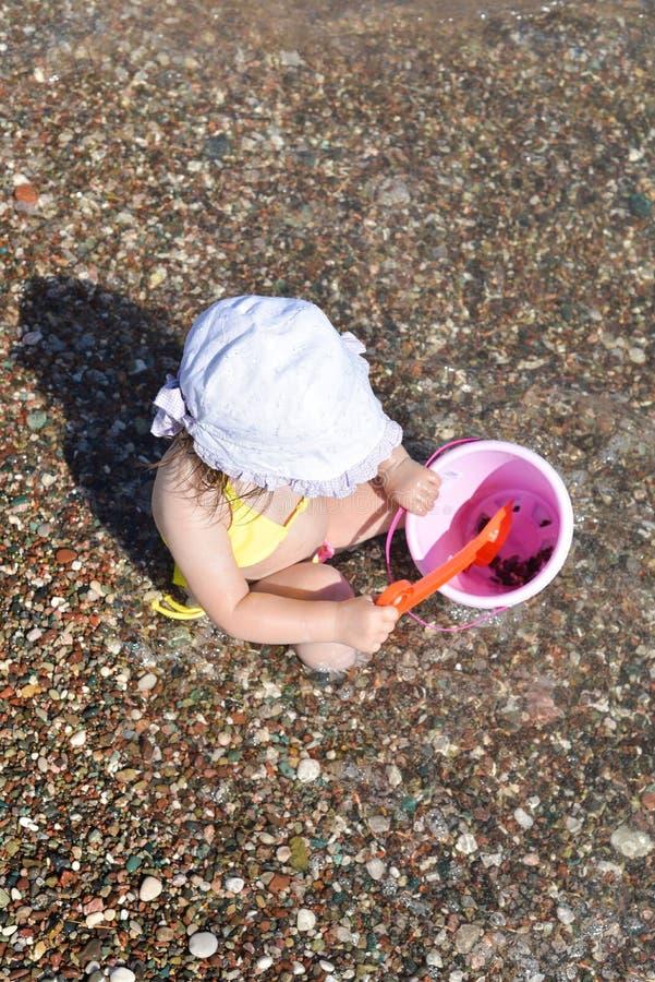 La petite fille mignonne joue avec le seau sur une plage, rassemblant r photo libre de droits