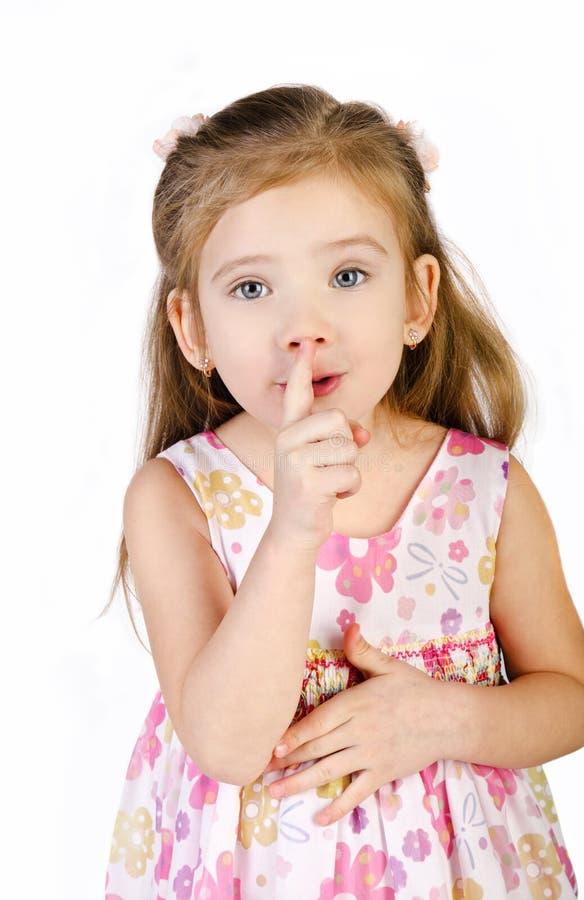 La petite fille mignonne juge son doigt près de la bouche d'isolement photo libre de droits
