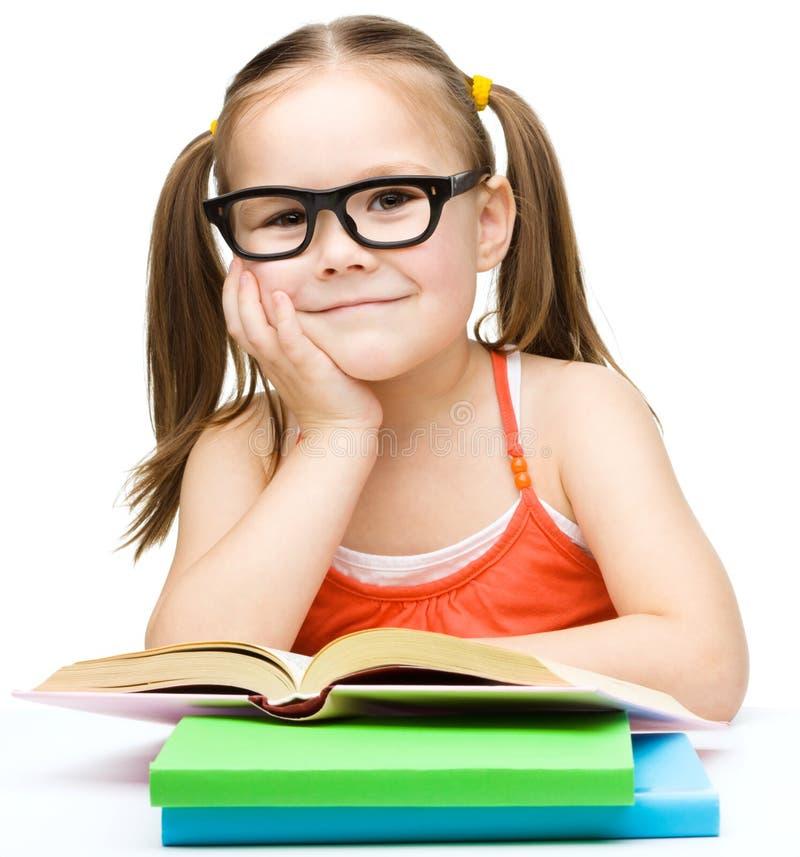 La petite fille lit un livre image stock
