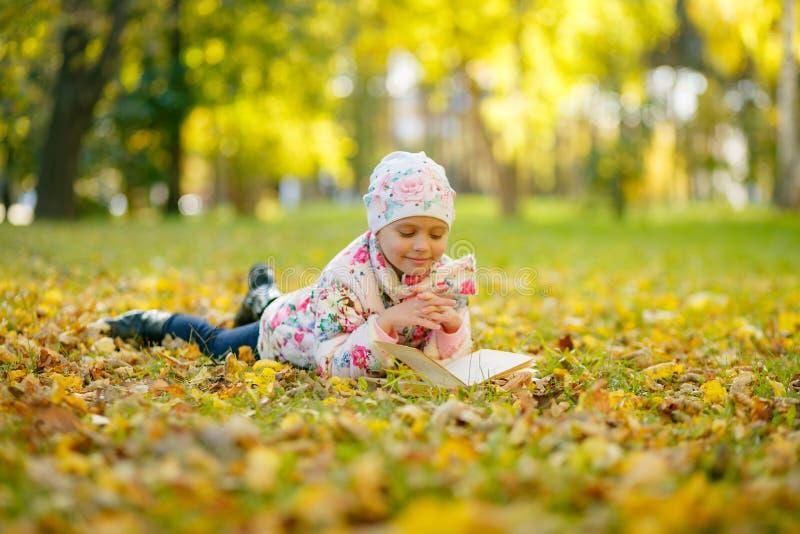 La petite fille mignonne lit un livre tout en s'étendant sur les feuilles d'automne jaunes photo stock
