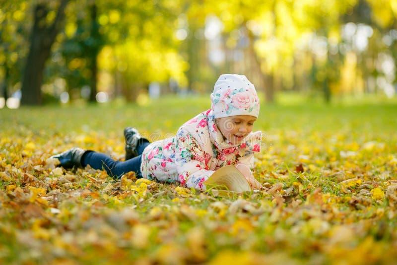 La petite fille mignonne lit un livre tout en s'étendant sur les feuilles d'automne jaunes images stock