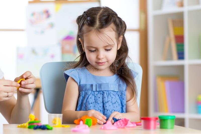 La petite fille mignonne moule de la pâte à modeler sur la table photographie stock