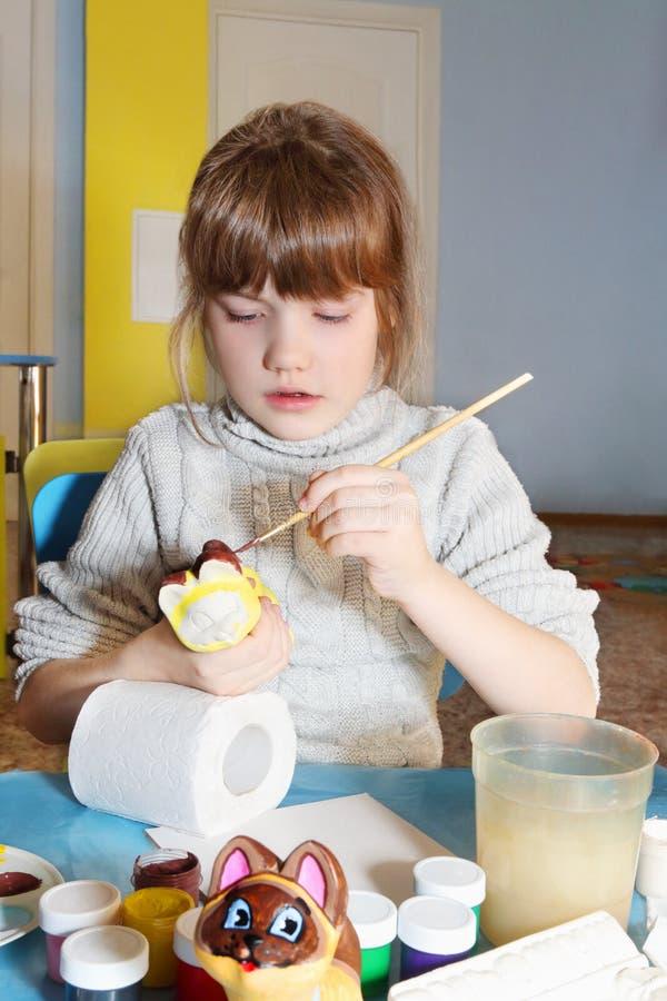 La petite fille mignonne peint la figurine de gypse du chat photo libre de droits