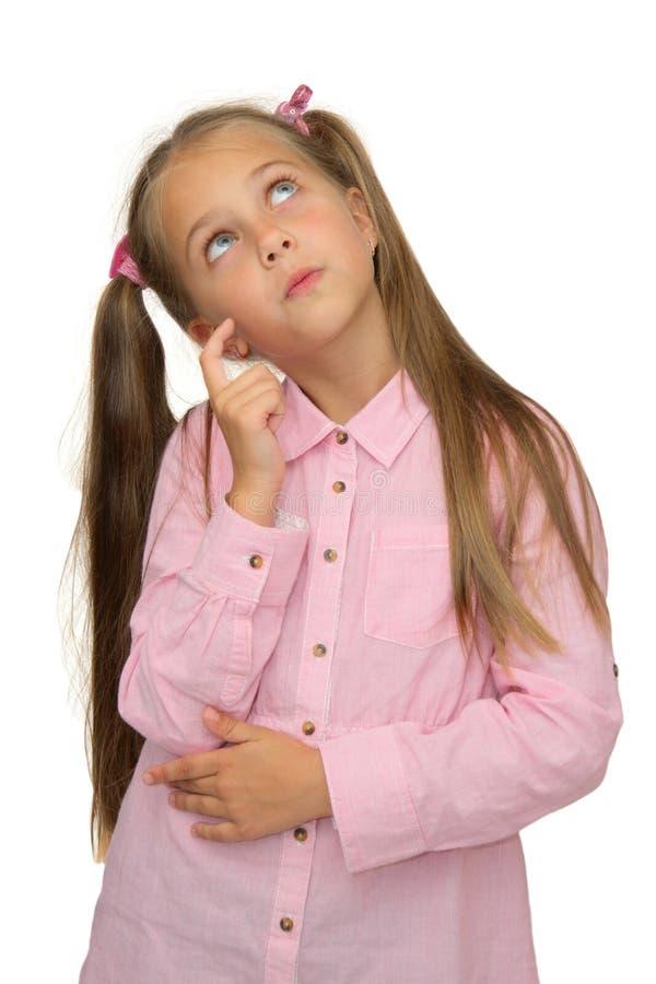 La petite fille mignonne pense le regard vers le haut sur le blanc photo libre de droits