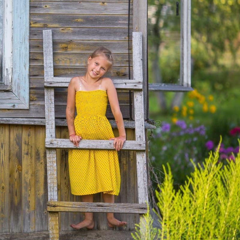 La petite fille mignonne se tient sur une échelle en bois au mur photos stock